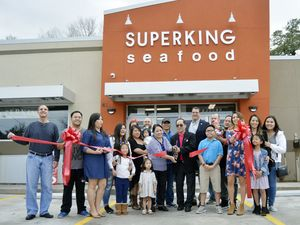 CELEBRATING -- The Nguyen family, Mayor Pete Panepinto, Greater Hammond Chamber of Commerce members and others stand outside the Superking Seafood building, in Hammond, for the ribbon-cutting ceremony Saturday. Photo by Emily Enfinger